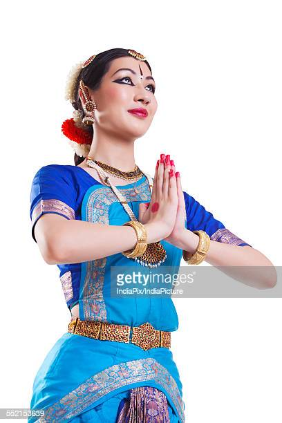 Bharatanatyam dancer in prayer position against white background
