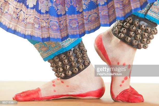 Bharatanatyam dancers feet performing over white background