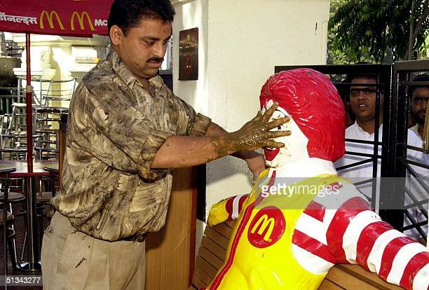 Bharatiya Janata Party activist smears cowdung on a likeness of Ronald McDonald fastfood giant McDonald's mascot, at a Bombay outlet 04 May 2001. The...