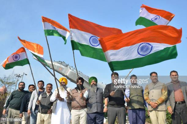 Bharatiya Janata Party activist wave Indian national flags in front of a fighter plane model as they celebrate the Indian Air Force strike launched...
