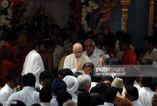 Bharatiya Janata Party Leader Lal Krishna Advani gestures as he leaves after paying homage after the final rituals of the burial of Hindu guru Sathya...