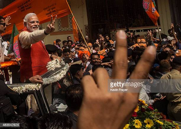 Bharatiya Janata Party leader Narendra Modi gestures to supporters as he rides in an open jeep on his way to file nomination papers on April 9 2014...