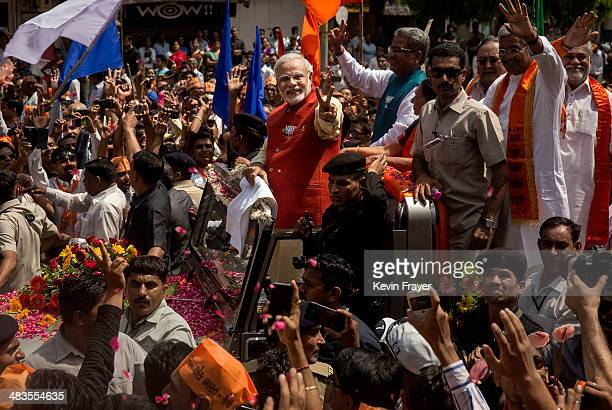 Bharatiya Janata Party leader Narendra Modi gestures to supporters on his way to filing his nomination papers on April 9 2014 in Vadodra India India...