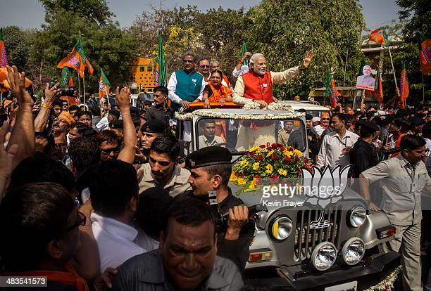 Bharatiya Janata Party leader Narendra Modi waves to the crowd as he rides in an open jeep on his way to file nomination papers on April 9 2014 in...