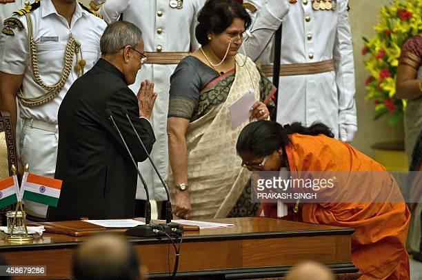 Bharatiya Janata Party leader Sadhvi Niranjan Jyoti gestures to greet Indian President Pranab Mukherjee during a swearingin ceremony at The...