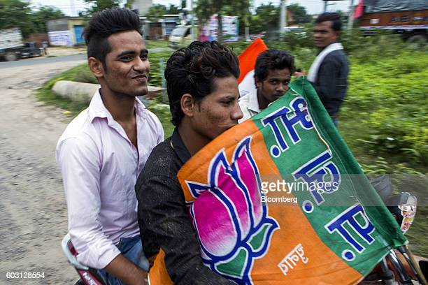 Bharatiya Janata Party members and supporters carry a party flag during a BJP motorcycle party rally near Aligarh Uttar Pradesh India on Tuesday Aug...