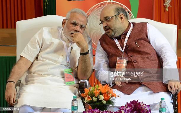Bharatiya Janata Party President Amit Shah talks with Indian Prime Minister Narendra Modi at a BJP National Council meeting at Jawaharlal Nehru...