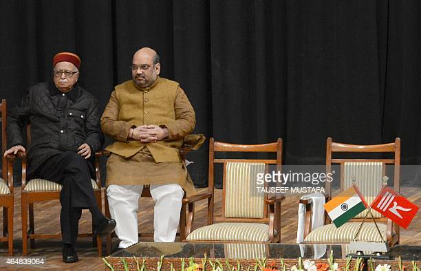 Bharatiya Janata Party senior leader Lal Krishna Advani and BJP President Amit Shah speak during a swearing in ceremony of the state assembly in...