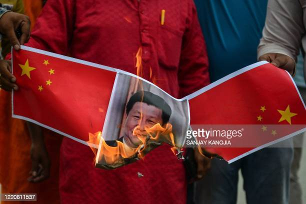 TOPSHOT Bharatiya Janata Party supporters burn posters and effigy of Chinese President Xi Jinping during an antiChina protest in Allahabad on June 17...