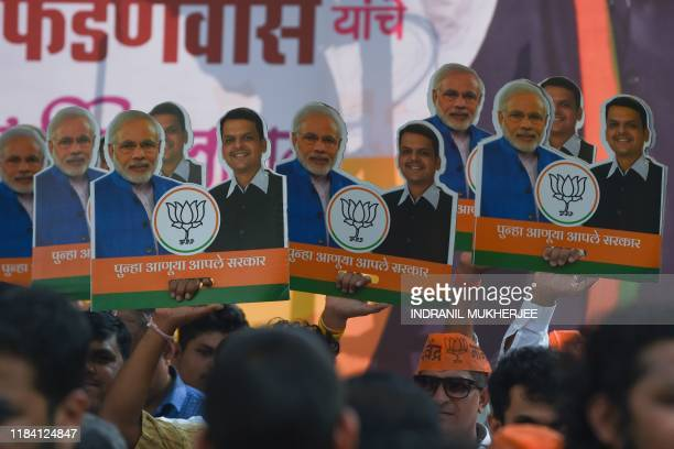 Bharatiya Janata Party supporters celebrate with posters of Indian Prime Minister Narendra Modi and Chief Minister of the western Indian state of...