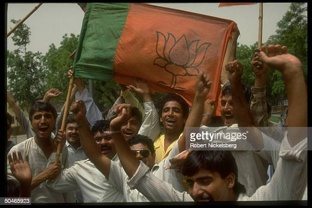 Bharatiya Janata Party supporters celebrating 2nd place in elections w green orange party flag Hindu natl party won 23% of vote up fr 114%