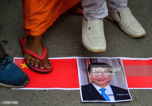 Bharatiya Janata Party supporters prepare to burn posters and effigy of Chinese President Xi Jinping during an antiChina protest in Allahabad on June...