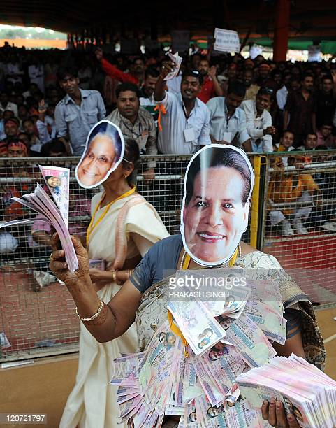 A Bharatiya Janata Party Youth Wing activist wearing a mask bearing the portrait of Congress President Sonia Gandhi poses with fake currency notes...