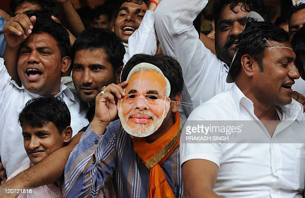 A Bharatiya Janata Party Youth Wing activist wearing a mask bearing the portrait of Gujarat state Chief Minister Narendra Modi listens to leaders'...