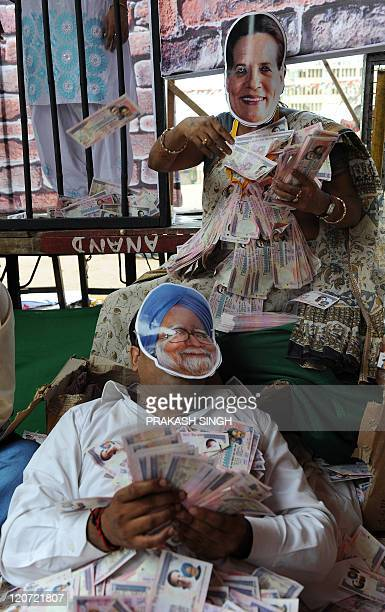 Bharatiya Janata Party Youth Wing activists wearing masks bearing the portrait of Indian Prime Minister Manmohan Singh and Congress President Sonia...