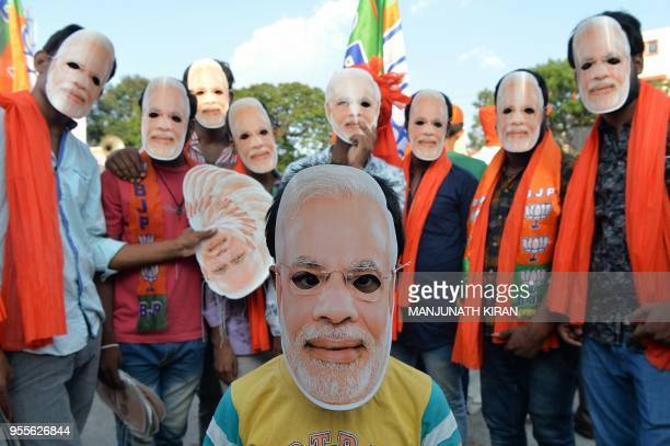 Bharatiya Janatha Party supporters wear masks of Prime Minister Narendra Modi during an election campaign of President Amit Shah for the forthcoming...