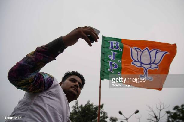 Bharatiya Janta Party or BJP supporter seen taking a selfie while holding a flag during the Show in Kolkata Bharatiya Janata Party president Amit...