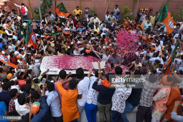 Bharatiya Janta Party president Amit Shah shows a victory sign as he is surrounded by his supporters at his arrival at the party headquarters on May...