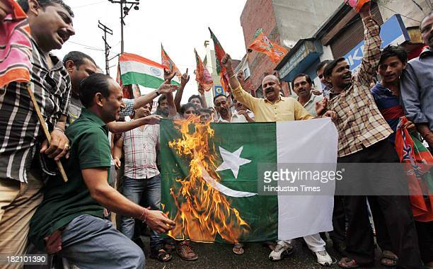 Bharatiya Janta Party Yuva Morcha activists burn the Pakistan flag during a protest against terrorist attack on September 27 2013 in Jammu India Four...
