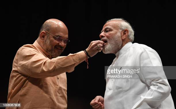 Bhartiya Janata Party President Amit Shah offers sweets to Indian Prime Minister Narendra Modi for winning the Noconfidence motion moved by...