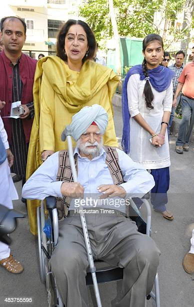 Bhartiya Janta Party candidate form Chandigarh Kirron Kher with her 101 years old father Thakar Singh, arriving to cast their vote at Government...