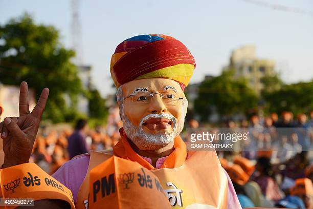 A Bhartiya Janta Party supporter wearing a mask of Indian Prime MinisterElect Narendra Modi gestures during a public meeting of Modi in Ahmedabad on...