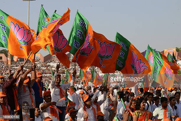 Bhartiya Janta Party supporters wave their party's flags while celebrating party's 33rd foundation day during a rally in Ahmedabad on April 6 2013...