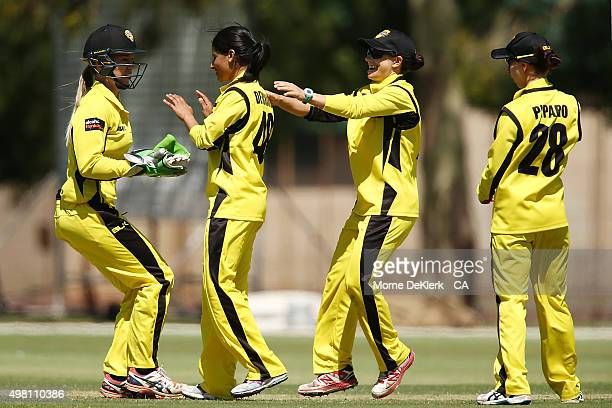 Bhavi Devchand of the Fury celebrates with teammates after getting the wicket of Hayley Matthews of the Roar during the WNCL match between Tasmania...
