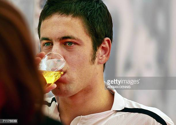 English midfielder Joe Cole takes a drink of juice as he departs a press conference at Mittelbergstadion in Buhlertal 11 June 2006 England team...