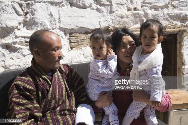 Bhumchu Zangmo mother of twins Nima and Dawa Pelden holds them as her husband Sonam Tshering looks on at Tachogang Lhakhang Monastery in Paro Valley...