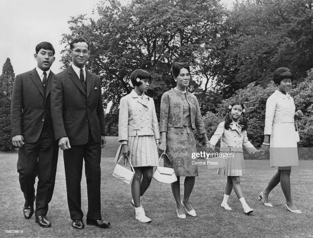 Bhumibol Adulyadej (1927 - 2016), King of Thailand, and Queen Sirikit with their children at a photocall at King's Beeches, their private residence in Sunninghill, Berkshire, 27th July 1966. Left to right, Crown Prince Maha Vajiralongkorn, the King, Princess Sirindhorn, the Queen, Princess Chulabhorn and Princess Ubol Ratana, 28th July 1966.