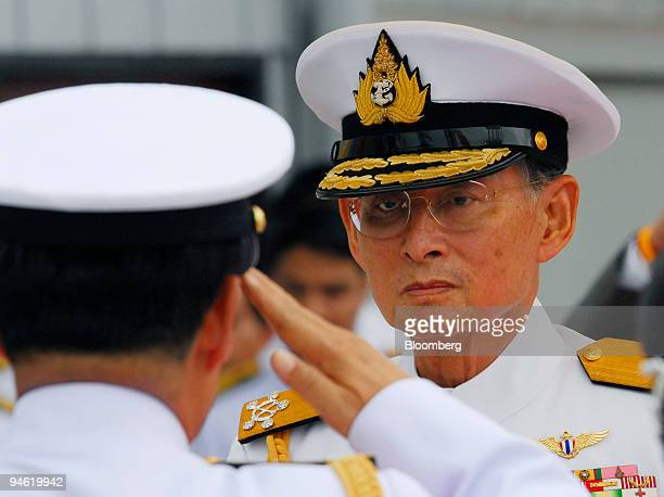 Bhumibol Adulyadej King of Thailand receives a salute from a Navy officer as he arrives for the inauguration of a Royal Thai Navy costal patrol boat...