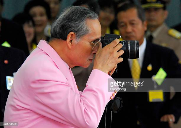 Bhumibol Adulyadej the King of Thailand takes a picture of thousands of well wishers as he leaves a hospital in Bangkok Thailand on Wednesday Nov 7...