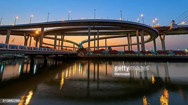 Bhumibol Bridge with skyline reflection at dusk in Bangkok, Thailand.