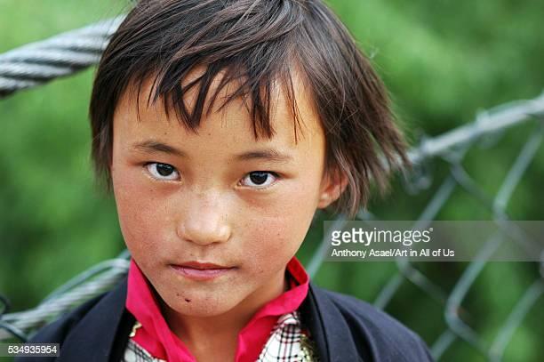 Bhutan Paro portrait of a short haired Bhutanese girl staring