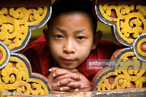 Bhutan, Thimphu, monk (9-11) peeking through ornate carving, portrait