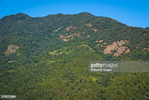 bhutan, trongsa, nimshong. view across valley to tiny kubdra village on steep hill. - trongsa district stockfoto's en -beelden