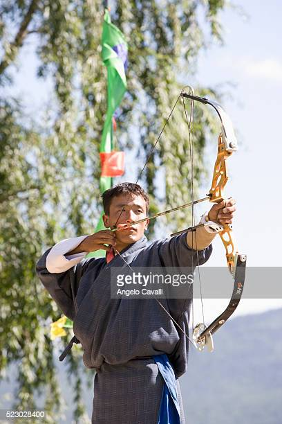 bhutanese archer in competition - bhutan stock pictures, royalty-free photos & images