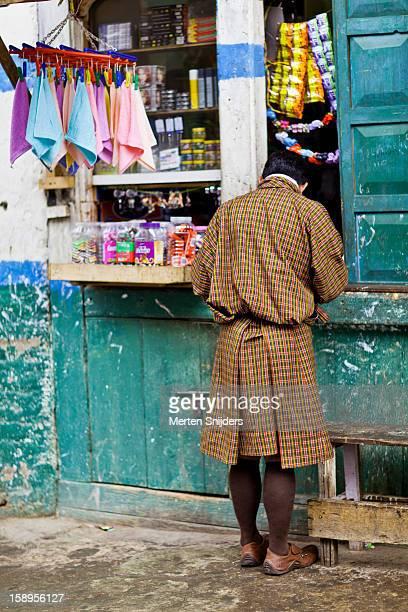 bhutanese man at convenience store - merten snijders photos et images de collection