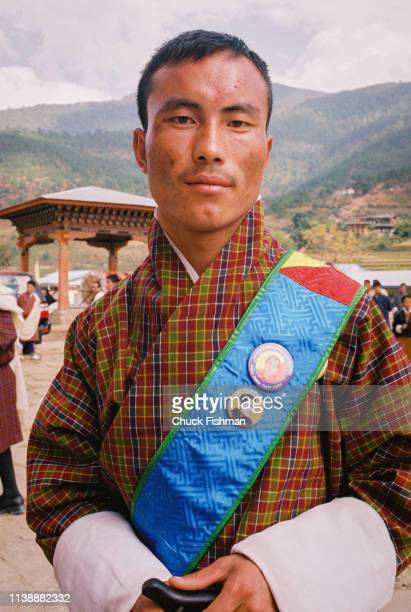 Bhutanese man outside Khuruthang Lhakhang wearing buttons with pictures of King Jigme Singye Wangchuck Punakha Bhutan 2004