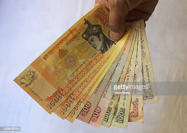 Bhutanese ngultrum banknotes of various denominations are arranged for a photograph in Thimphu Bhutan on Wednesday Feb 15 2012 Bhutan with a...