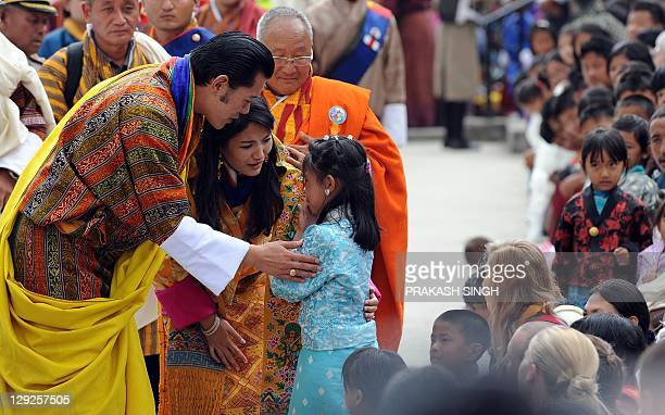Bhutanese royal couple King Jigme Khesar Namgyel Wangchuck and Queen Jetsun Pema speak to a young girl as they greet the crowd during a ceremony at...
