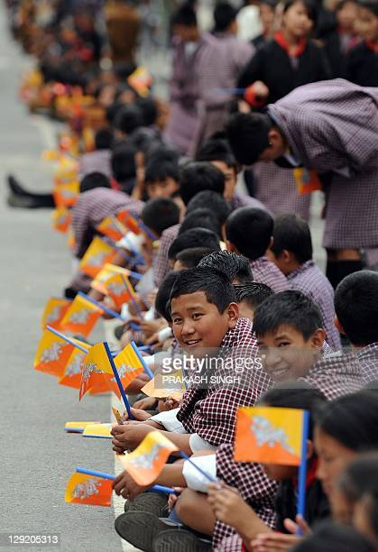 Bhutanese school children wave the national flag of Bhutan as they wait for the arrival of the royal couple King of Bhutan Jigme Khesar Namgyel...