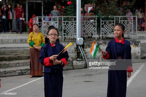 Bhutanese students wave Indian and Bhutanese flags along a road as the convoy of Indian Prime Minister Narendra Modi drives past on his way to...