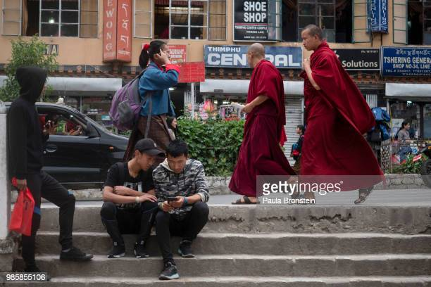 """Bhutanese teens are seen hanging out using mobile phones as monks stroll by on June 14 in Thimphu, Bhutan. While many are expected to wear the """"Gho""""..."""