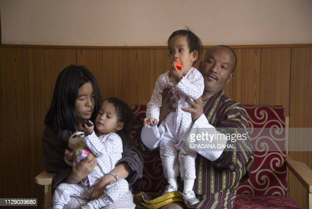 Bhutanese twins Nima and Dawa Pelden look on as mother Bhumchu Zangmo and father Sonam Tshering hold them in a guest house in Thimphu on March 7 2019...