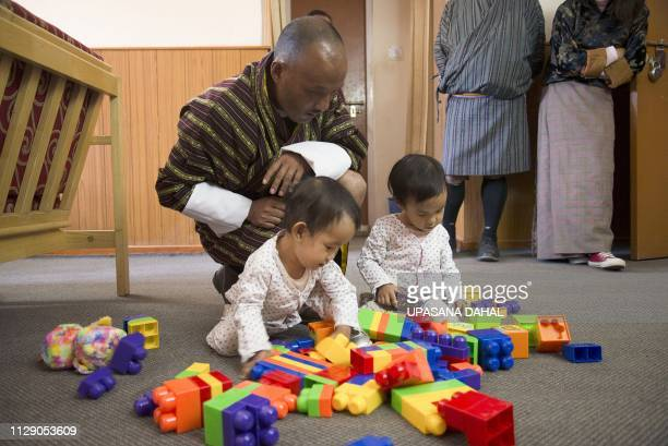 Bhutanese twins Nima and Dawa Pelden play as their father Sonam Tshering looks on in a guest house in Thimphu on March 7 2019 Bhutan's first...