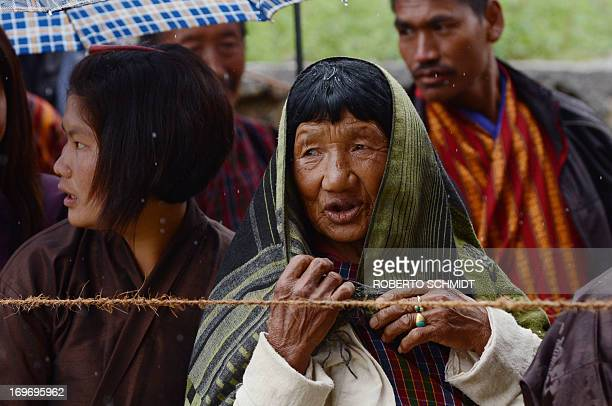A Bhutanese villager waits in line outside a polling station to cast her vote under light rain in Paro on May 31 2013 Bhutan begins its second ever...