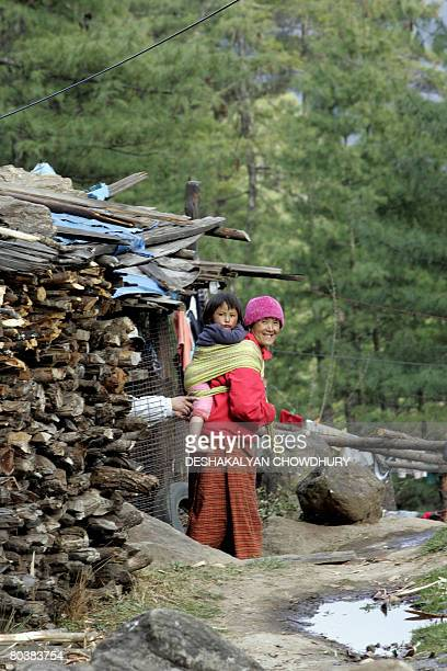 A Bhutanese woman gestures as she carries her child on her back as she works in a village on the outskirts of Thimphu on March 26 2008 The tiny...