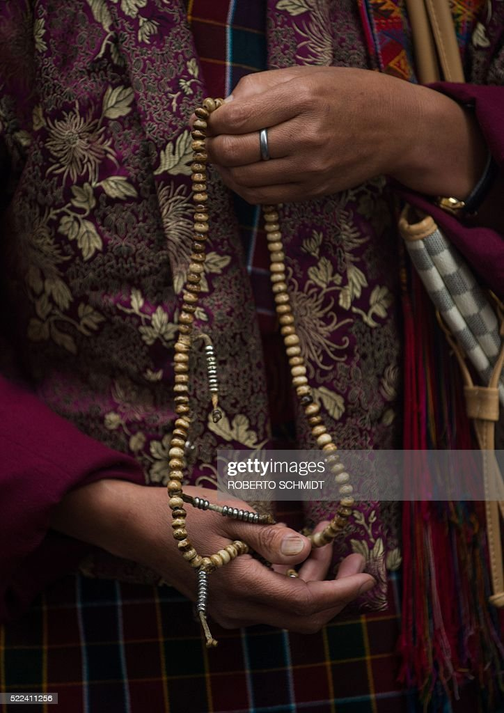 A Bhutanese woman holds prayer beads in her hands as she and other
